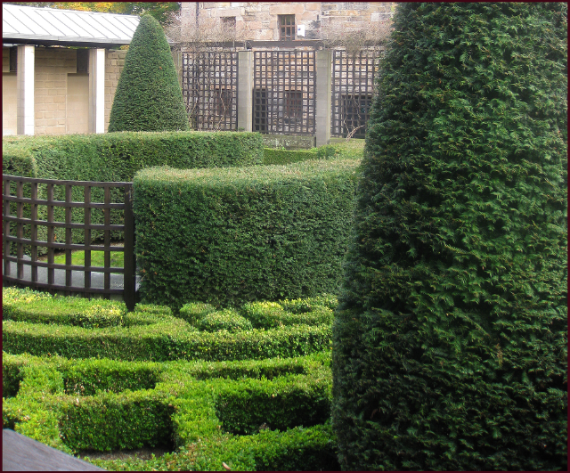 Perfectly trimmed hedges, upright evergreens, lattuce fence panels and brick walls provide formal sturcutre in the vertical plance while th wlow parterres [rovide the flooring in this old world courtyard. Photo: Evelyn Steinberg.